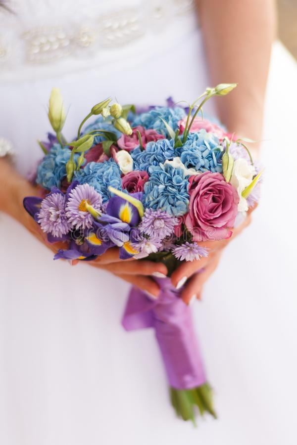 Wedding bouquet in pink and blue colors in the hands of the bride. Wedding bouquet in pink and blue colors of hydrangeas, lisianthus, irises, roses and stock image