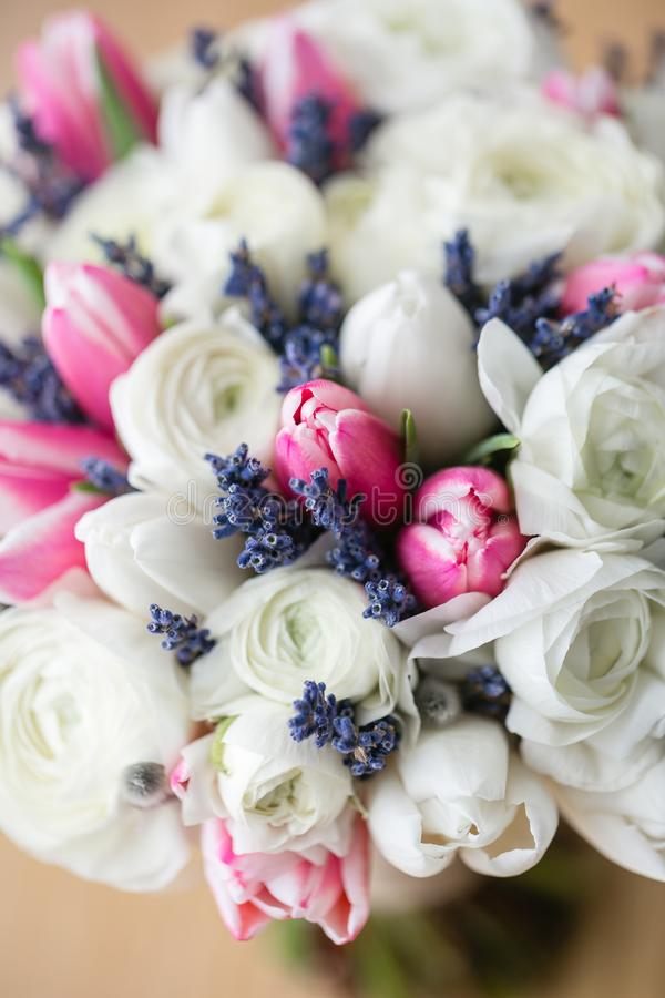 Wedding bouquet of pink tulip and white buttercup. Modern bridal bunch. Dry lavender stock photography