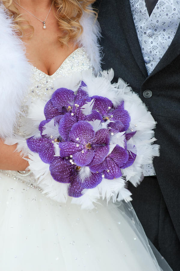 Wedding bouquet of purple orchids and feathers stock photos