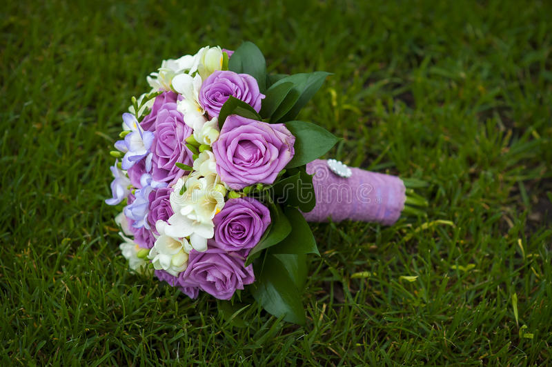 Wedding Bouquet Of Purple And White Roses Lying On Grass Stock Photo