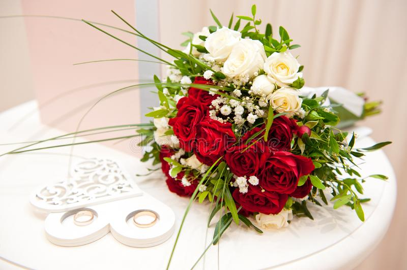 Wedding bouquet of red roses, white daisies and other flowers and wedding rings stock photo