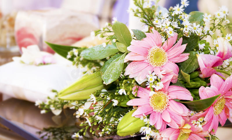 Wedding bouquet and ring pillow in background stock image
