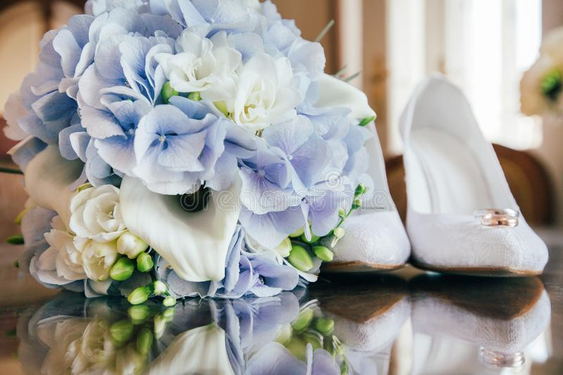 Wedding bouquet, rings and shoes. Details for marriage and for married couple royalty free stock photography