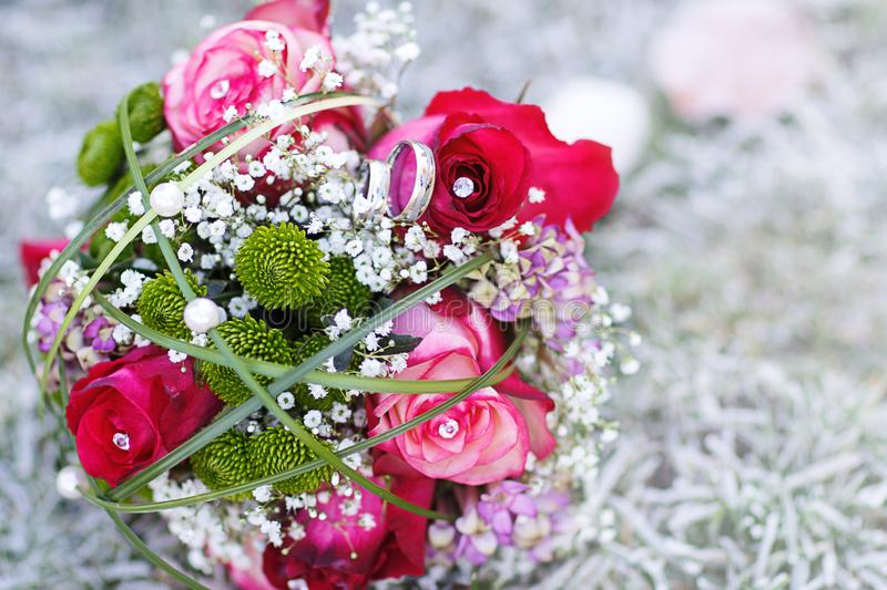 Wedding bouquet with rings. On the frozen grass royalty free stock photography