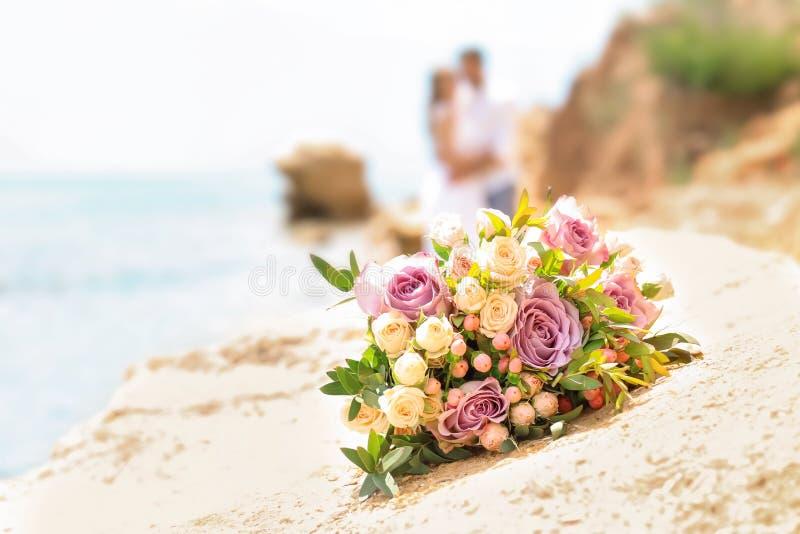 Wedding bouquet on rocky beach stock image