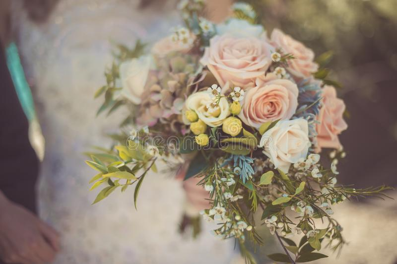 Wedding bouquet of rose in bride`s hands. A flower bouquet is a creative arrangement. Flower bouquets can be arranged for homes or public buildings, or may be royalty free stock photography