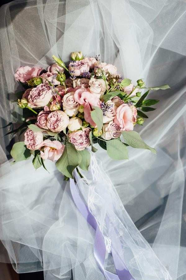 Wedding bouquet of roses and peonies lies on tulle on the chair royalty free stock images