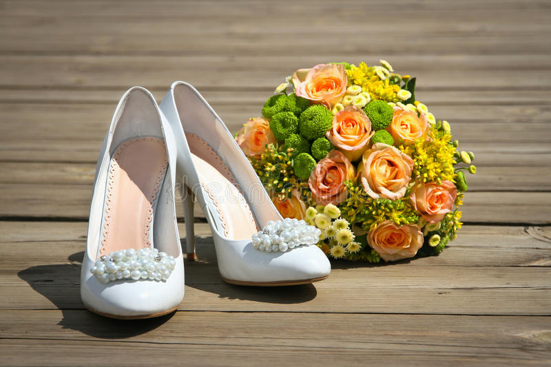 Wedding bouquet & shoes on a wooden platform stock images