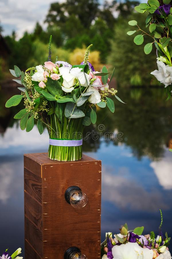 Wedding bouquet standing on unusual lamp outdoors royalty free stock photography
