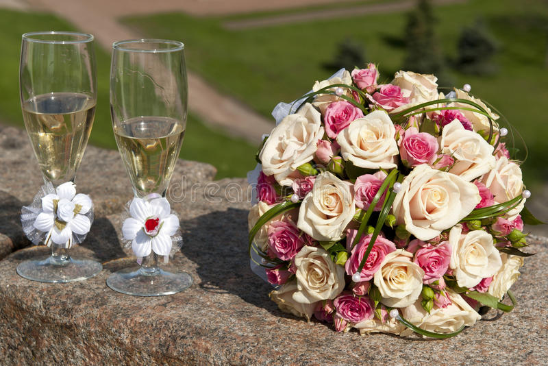Wedding Bouquet Beside Tall Wine Glasses stock images
