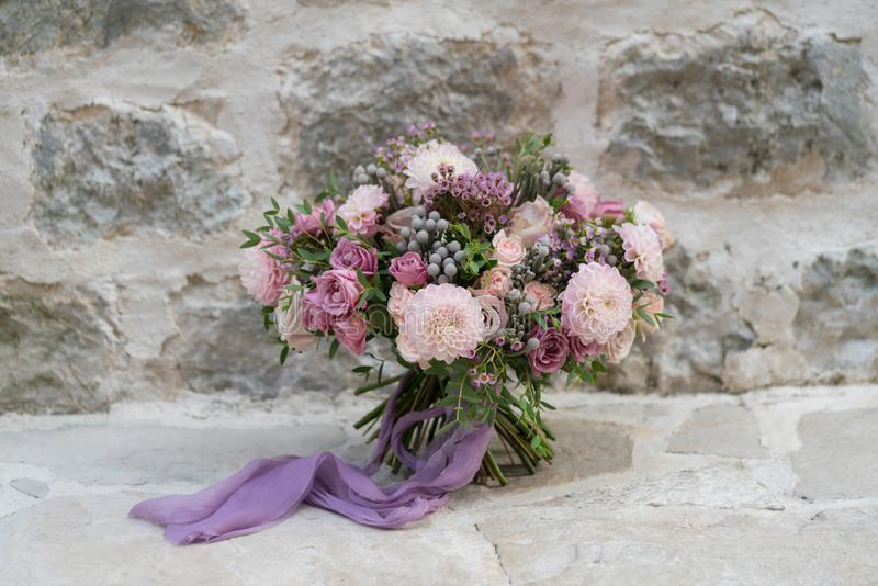Wedding bouquet of various flowers on a stone wall background stock image