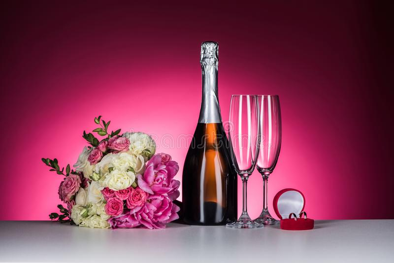Wedding bouquet, wedding rings and champagne. On pink stock photo