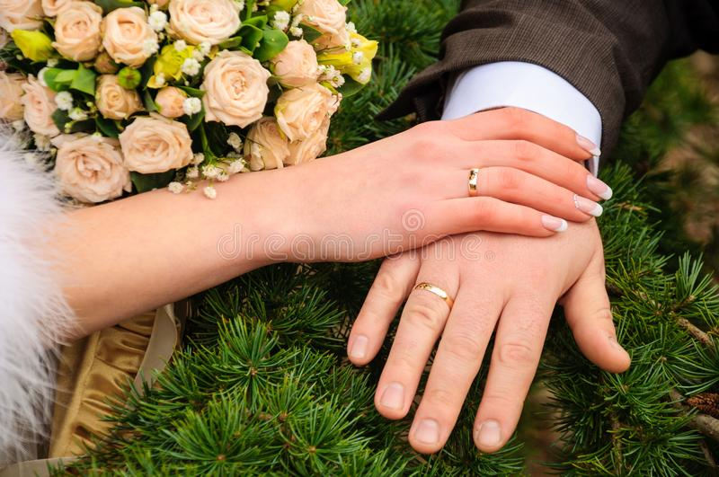 Wedding bouquet and wedding rings on the hands stock images