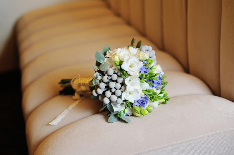Wedding bouquet of white flowers lying on the sofa