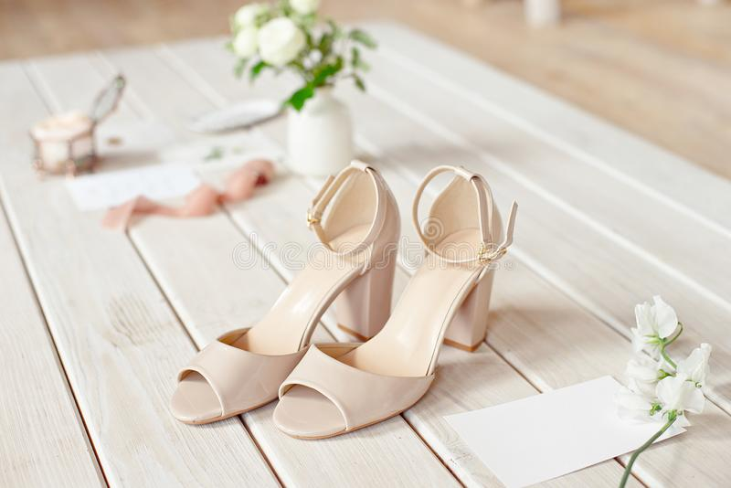 Wedding bouquet of white flowers, shoes and wedding rings on a wooden background. stock photography