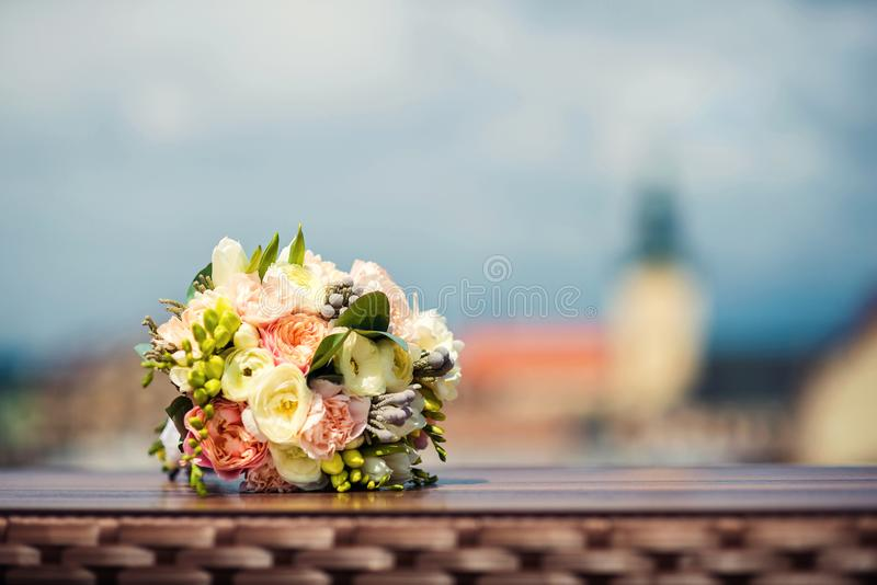 Wedding bouquet of white and pink peonies lies on a table on the background of the city view royalty free stock images