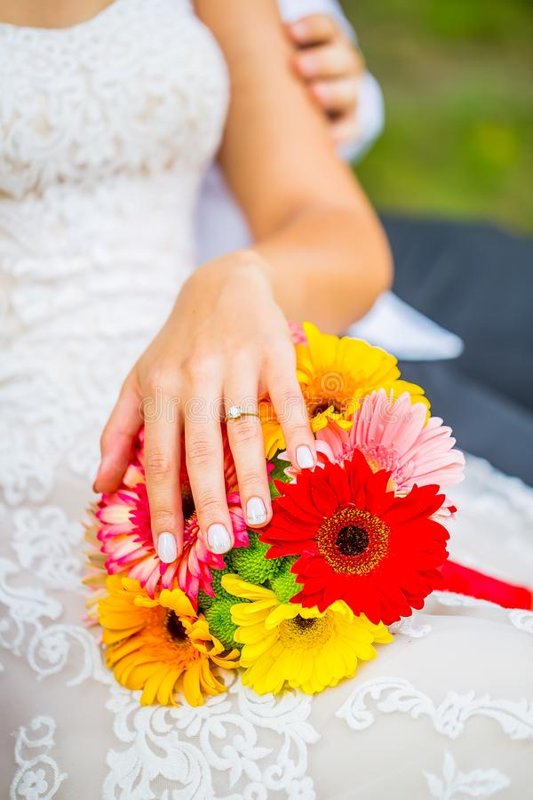Wedding bouquet with bride hand with ring royalty free stock image