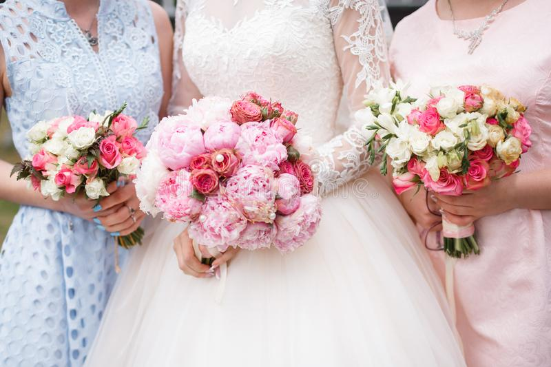 Wedding bouquets at the bride and bridesmaids. A bride in white and two girlfriends in blue and pink lace dresses are holding bouquets of delicate flowers of stock image