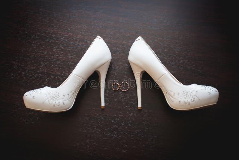 Wedding bridal ботинки и кольца на темной деревянной предпосылке стоковая фотография rf