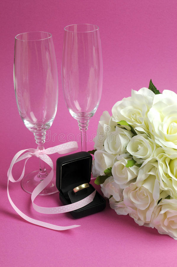 Wedding bridal bouquet of white roses on pink background with pair of champagne flute glasses - vertical.