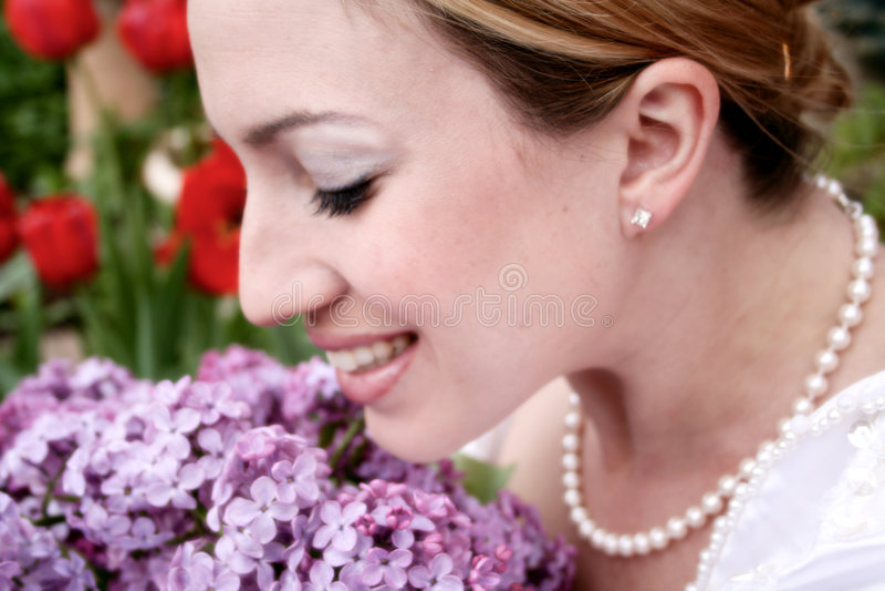 Wedding Bride 2. Blushing bride smiles as she smells her lilac wedding boquet royalty free stock image
