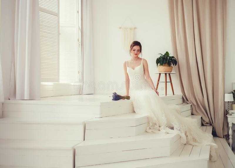 Bride in beautiful dress sitting on sofa indoors. Wedding. Bride in beautiful dress sitting on sofa indoors in white studio interior like at home. Trendy wedding royalty free stock photo