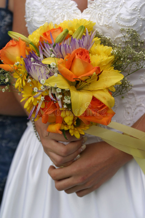 Wedding Bride Bouquet. The bride holding a beautiful bouquet of orange, yellow and purple flowers. If you like this photo, please see my portfolio for more plus stock photo