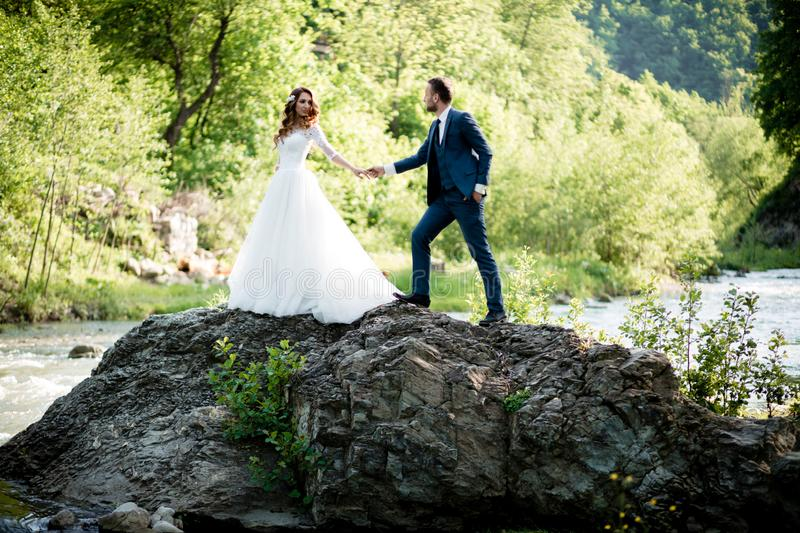 Wedding. Bride and groom holding hands and walk near river royalty free stock photos