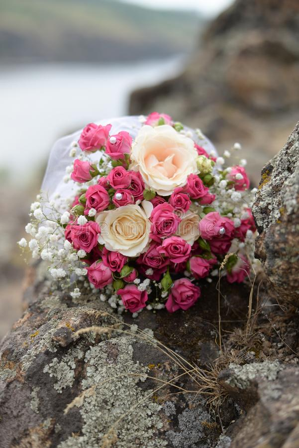 Wedding bride`s bouquet of pink and white flowers roses lies on a log by the lake . wedding background with copy space stock image