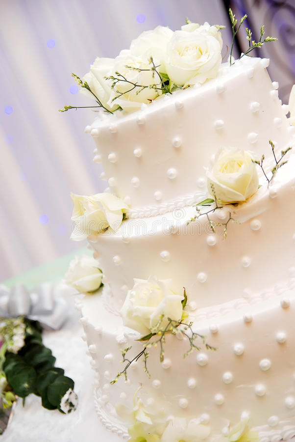 Wedding Cake. A white wedding cake, shallow depth of field with the focus on the center of the cake. white roses on top stock photography