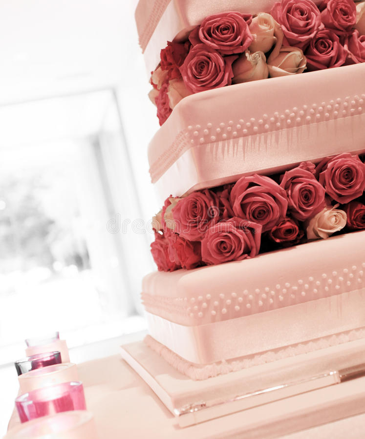 Wedding cake with red and pink roses. A stunning wedding cake ready to be cut decorated with pink roses on a silver platter stock photos