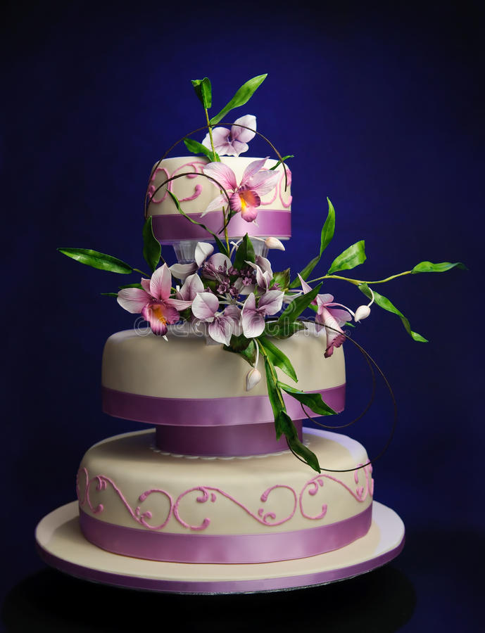 Wedding cake. Three layered lilac bridal cake decorated with a bouquet of summer flowers; Orchids and Hydrangea, on a bluw background. Flowers are all hand made