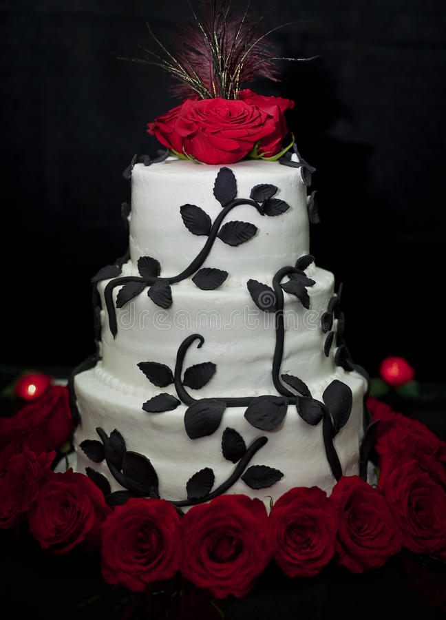 Wedding cake. A tiered wedding cake in black and white with red roses and a peacock feather top on a black bakground royalty free stock photos