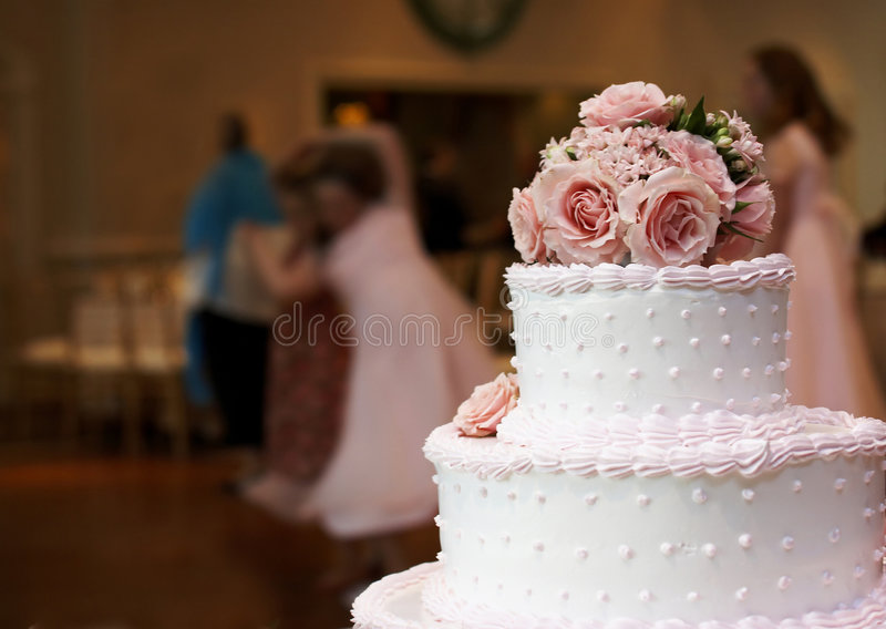 Wedding cake. A pink and white wedding cake with roses on top and people in the background dancing stock photos