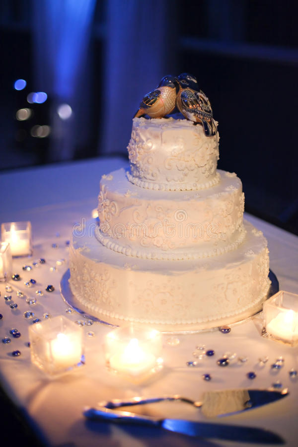 Wedding cake. A tiered wedding cake in with love birds on top and surrounded by candles royalty free stock photography