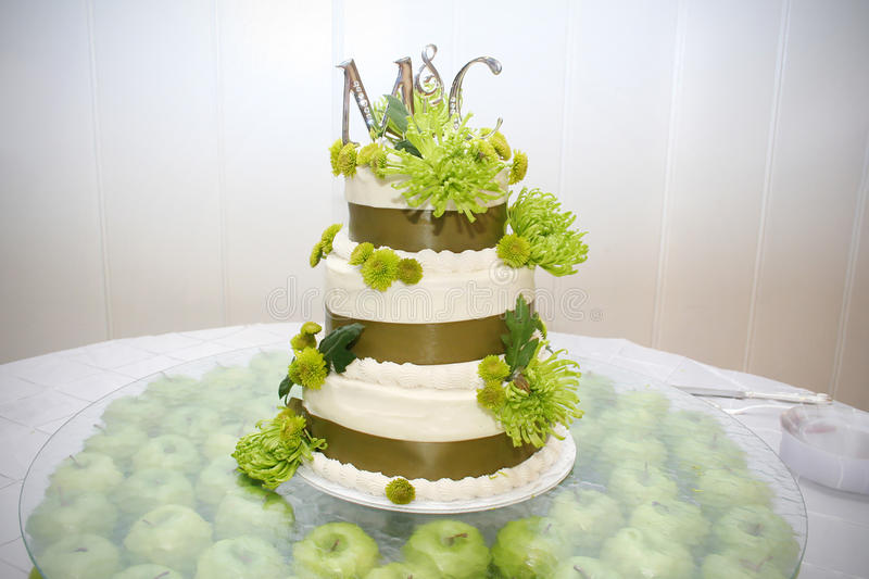 Wedding Cake. A wedding cake is decorated with green and brown and sits on a tray with green apples underneath royalty free stock photography