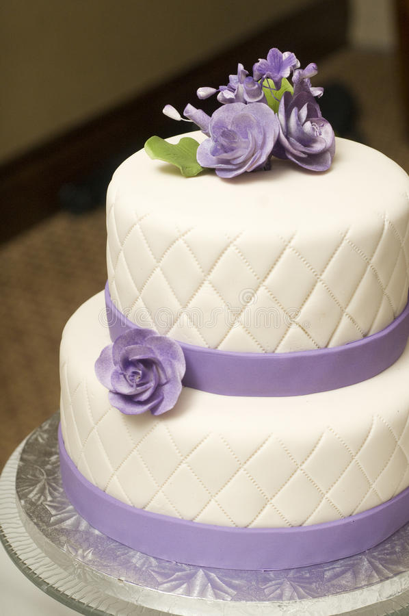 Wedding cake. Tall wedding cake with purple ribbon and flower decorations royalty free stock photo