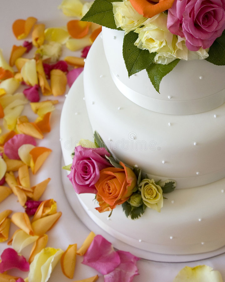 Wedding cake. Three-tiered round wedding cake covered in white rolled fondant and decorated with brightly colored fresh roses