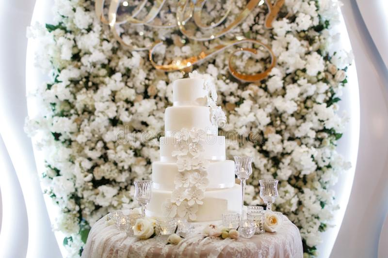 Wedding cake on the background of the flower arch stock images
