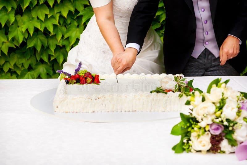 bride and groom cutting wedding cake stock image