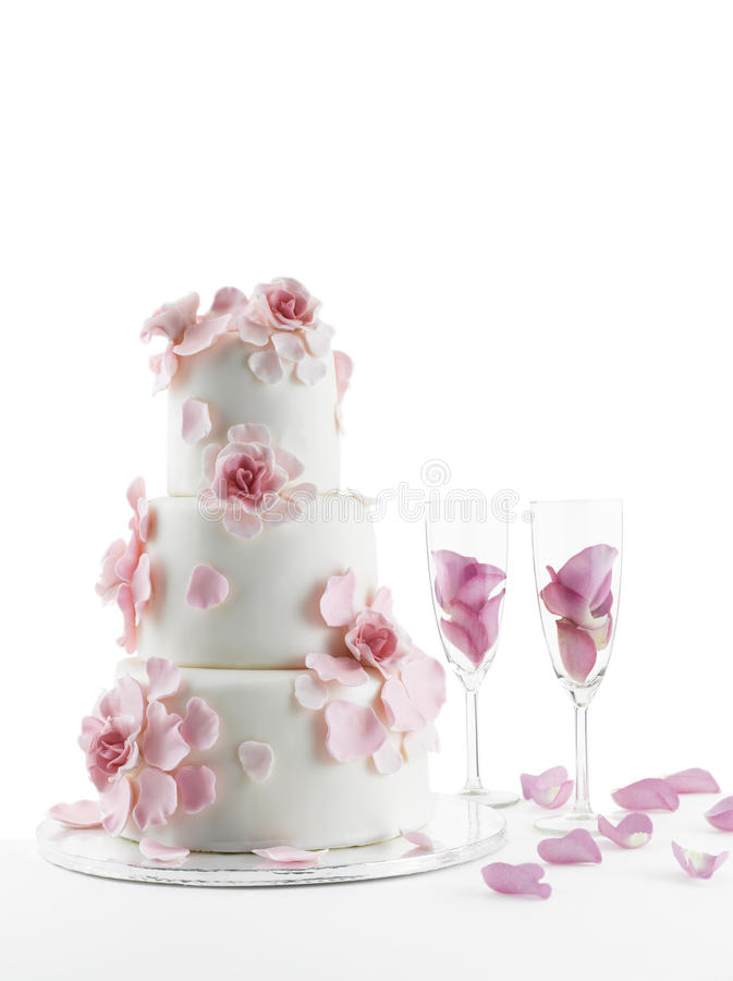 Wedding cake and champagne. Luxurious wedding cake with flowers and two champagne flute glasses with rose petals; white studio background with copy space royalty free stock photography