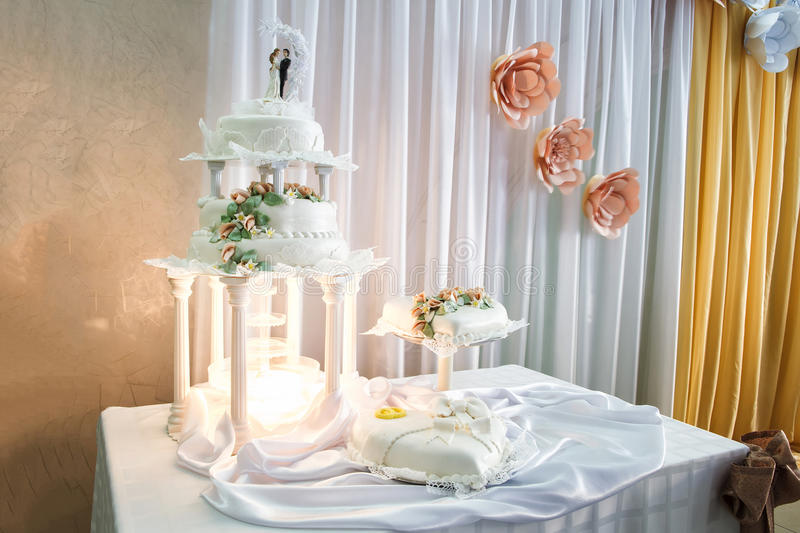 Wedding cake decoration of champagne fountain in lights and wedding cakes around royalty free stock photography