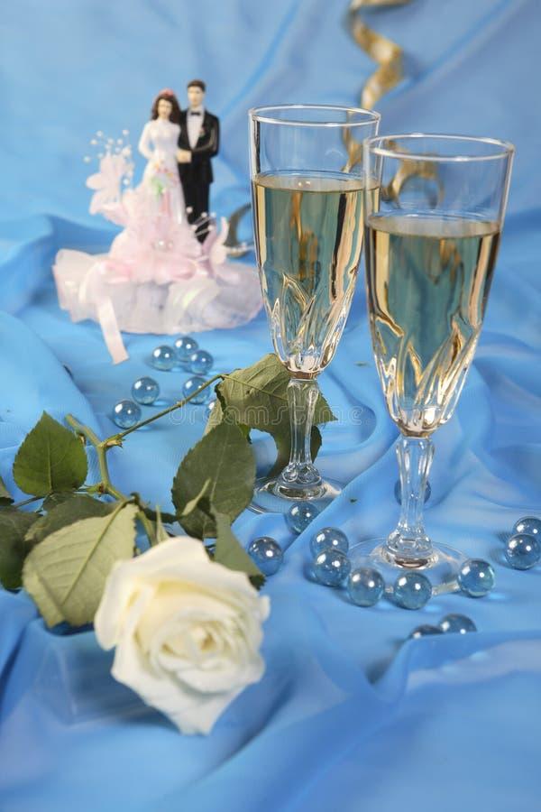 Wedding cake dolls, rose. A photo of wedding cake dolls, rose and glasses over blue stock images