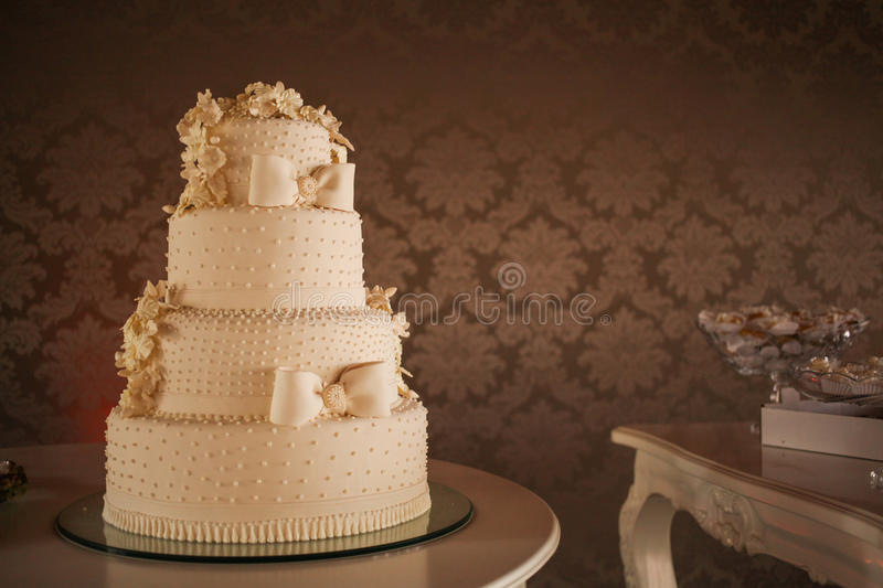 Wedding Cake. An elegant cake for a wedding against a beautyfull wall royalty free stock photography