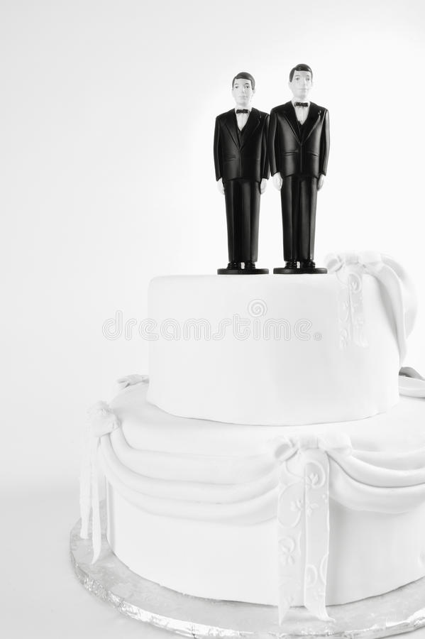 Wedding Cake Gay Couple. White wedding cake with a gay couple two men in tuxedos on top. LGBT same-sex gay marriage concept. Same sex marriage is legal in royalty free stock photo