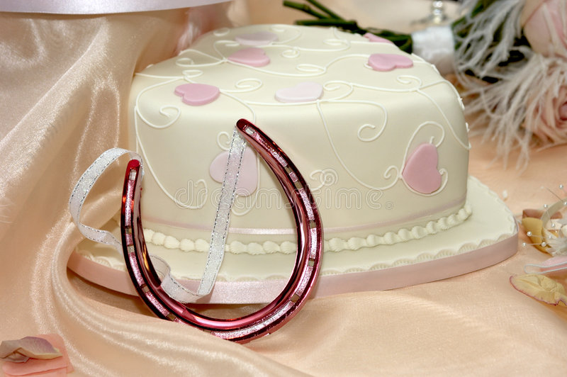 Wedding cake and horse shoe charm stock image