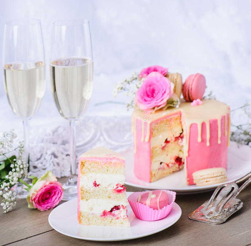 Wedding cake with pink frosting. And white chocolate ganache, decorated with flowers and macaroons. Wedding gown in the background stock photos