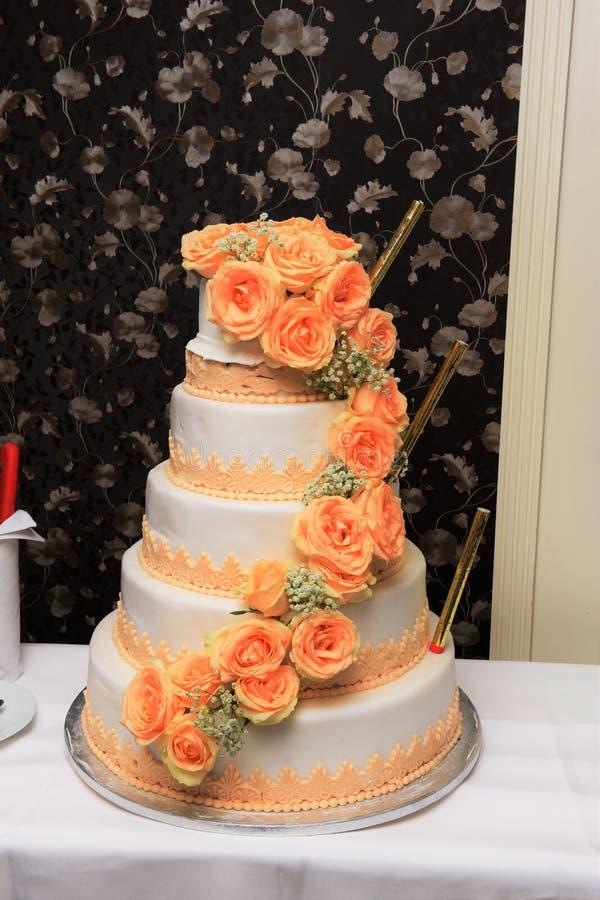 Wedding cake. Tall wedding cake decorated with natural orange roses and greenery stock image