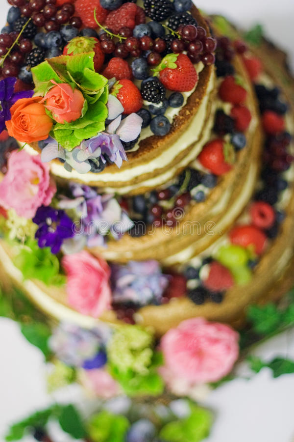 Wedding cake. Tall wedding cake with pink roses and white flower and fresh forest fruit decorations stock photo