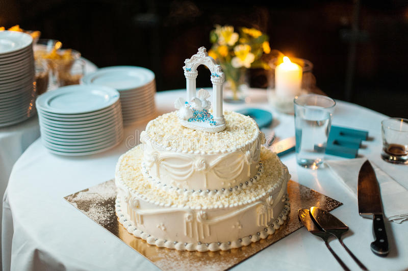 Wedding cake with two white doves on top. White wedding cake with two white doves on top royalty free stock photography